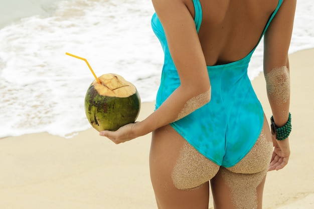 Female buttocks and coconut drink