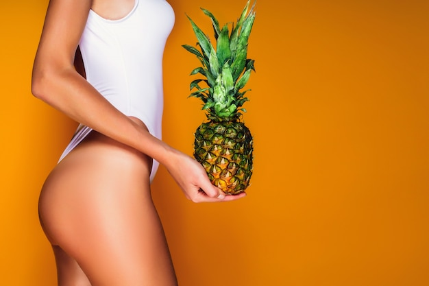 Female buttocks, sexy ass. young sporty woman holding a pineapple in her hand.