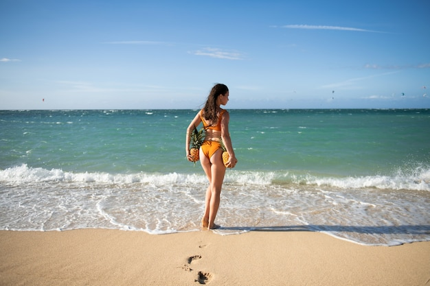 Female buttocks in swimsuit, sexy ass. woman holding a pineapple on the dominican or hawaii beach tropical background with copyspace.