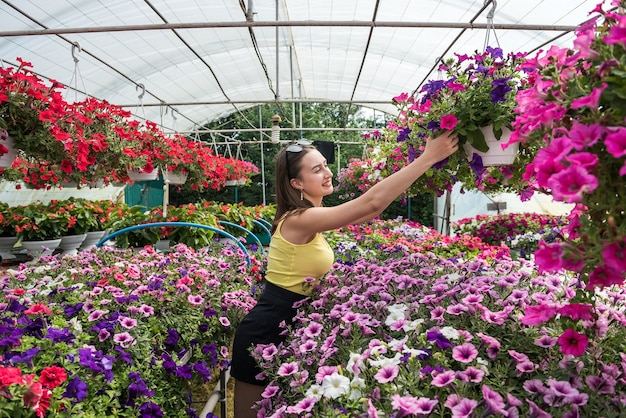 Покупательница выбирает красивые цветы в оранжерее