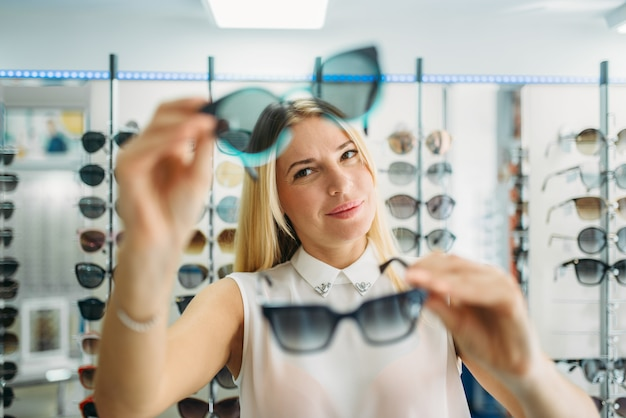 Female buyer chooses sunglasses in optics store, showcase with spectacles