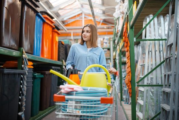 정원사를위한 상점에서 원예 도구를 선택하는 여성 구매자. 화초 재배, 꽃집 악기 구매를 위해 상점에서 장비를 구입하는 여성