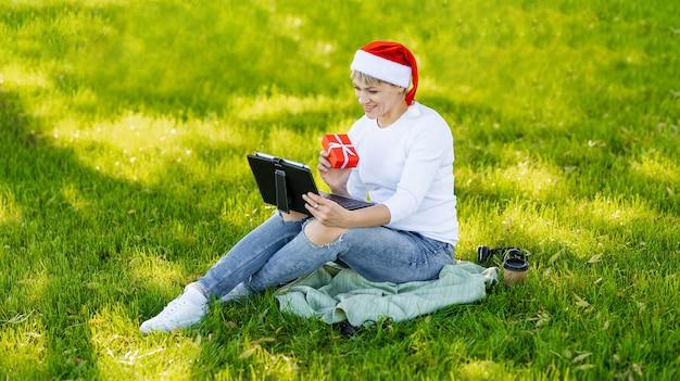 Покупатель женского пола делает заказ на ноутбуке. сезонные скидки. праздничные распродажи