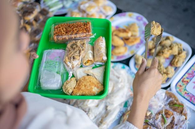 Покупательница использует щипцы-щипцы, чтобы выбрать и положить жареную еду на пластиковый поднос.