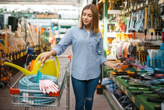 庭師のための店でガーデニングツールを購入するカートを持つ女性のバイヤー。花卉園芸、花卉楽器の購入のために店で機器を選ぶ女性