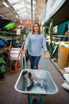 庭師のための店で庭のカートを持つ女性のバイヤー。花卉園芸用の店で機器を購入する女性、花卉楽器の購入