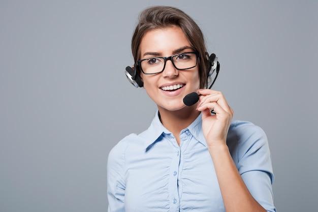 Агент женского call-центра позирует с наушниками с микрофоном