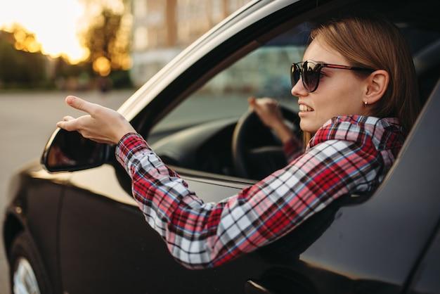 Female car driver in sunglasses, boorish behavior
