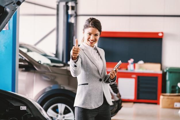 カーサロンのガレージに立って親指を立てる女性の車の売り手。車はすべてセットされ、修理されています。