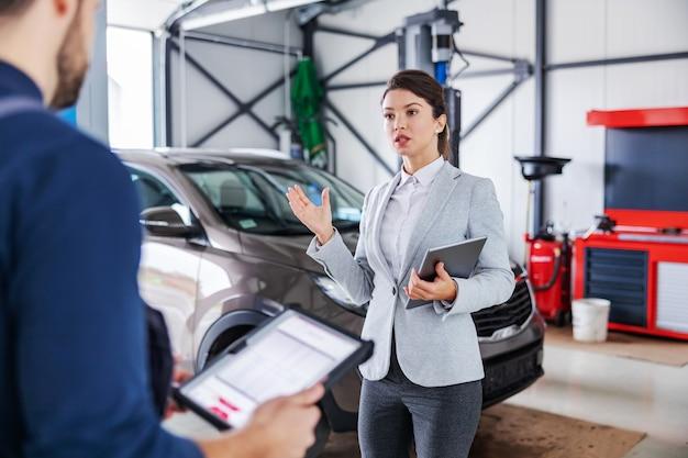 자동차 살롱의 차고에 서서 자동차 수리에 대해 정비사와 이야기하는 여성 자동차 판매자