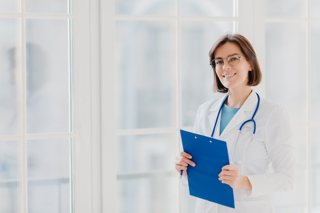 Female cardio therapeutist wears round glasses, white medical coat and phonendoscope, writes with pen in clipboard,