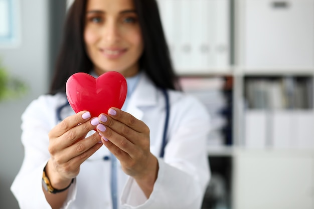 Female cardiolog holding in arms red toy heart