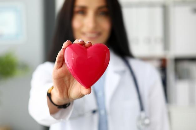 Женский кардиолог держит в руках красное игрушечное сердце