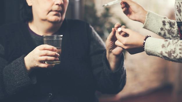 年配の女性患者に薬を与える女性介護者