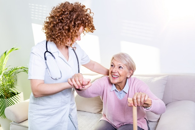 Female caregiver helping senior woman get up from couch in living room. smiling nurse assisting senior woman to get up.