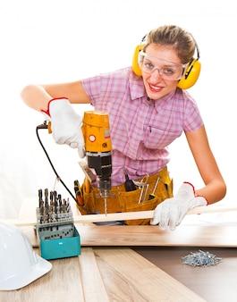 Женский плотник на работе, используя ручной сверлильный станок
