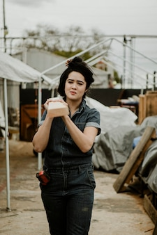 Female carpenter carrying a lumber on her shoulder