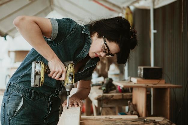 Female carpenter drilling a lumber