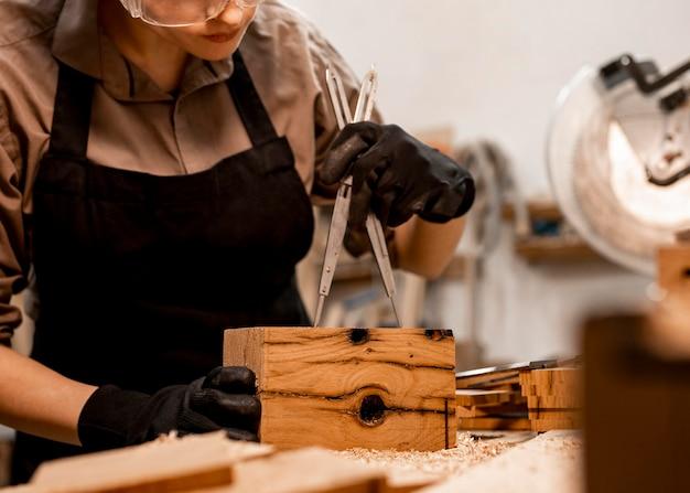 나무 조각을 측정하는 사무실에서 여성 목수