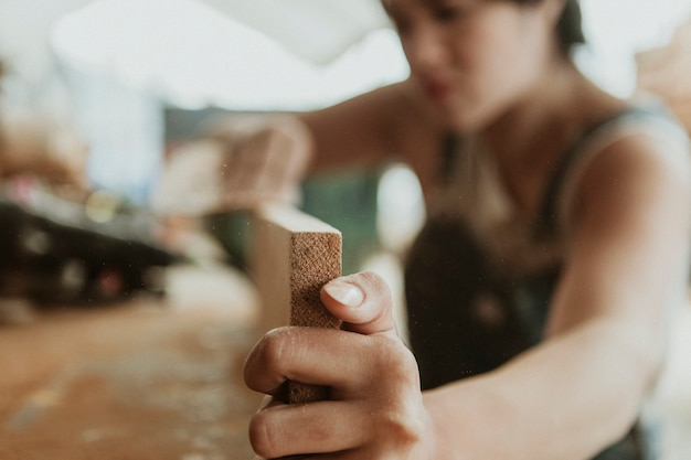 Female carpenter smoothing the lumber with a sanding disc