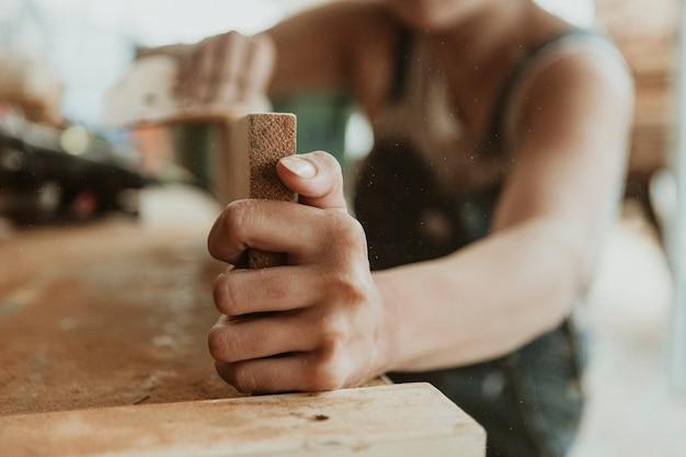 サンディングディスクで材木を滑らかにする女性の大工