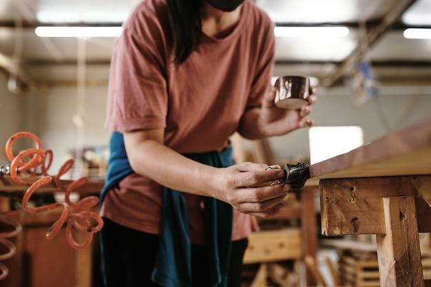 고객을 위한 가구 품목 작업 시 여성 목수 니스 칠하기