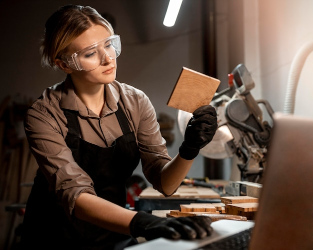 Female carpenter with safety glasses looking at piece of wood in the studio