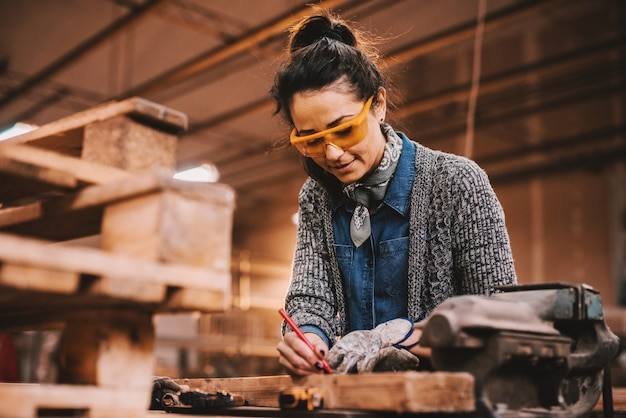 Female carpenter working in workshop. female doing male's work concept.