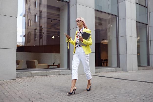 スマートフォンで街を歩きながら物を運ぶ女性