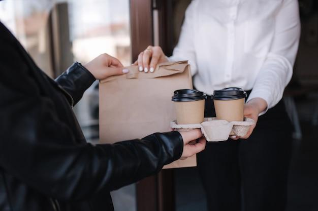 Женщина-кассир в маске для лица, подающая кофе и пакет с едой в кафе для клиентов, открытое после