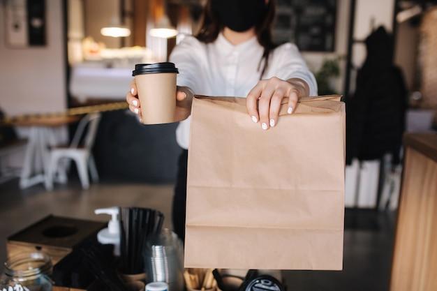 Женщина-кассир с маской для лица подает кофе и еду в магазин, открытый после блокировки.