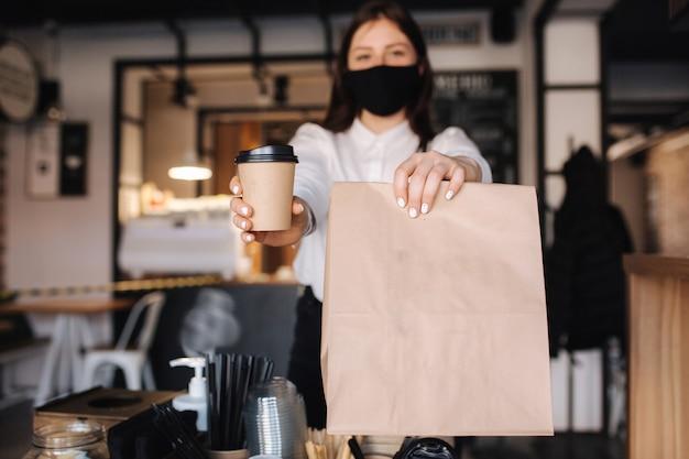 Женщина-кассир с маской для лица подает кофе в магазин, открытый после блокировки, женщина держит пакет