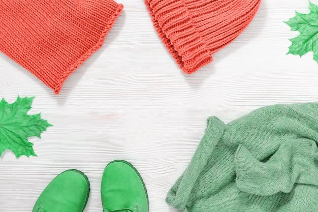 秋の天気、ファッショングリーンレザーブーツ、暖かいニットセーター、キャップ、スヌードピンク色の女性のカジュアルなカラフルな服。上からの眺め。コピースペース。