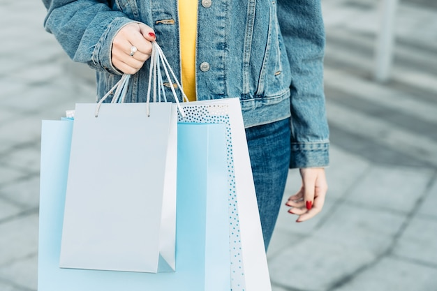 Female casual lifestyle assortment of paper bags in hands