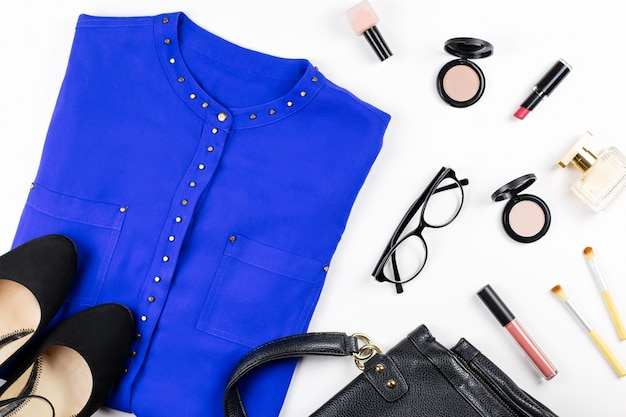 Female casual office style clothing and accessories -purple shirt, heeled shoes, handbag, make up items.