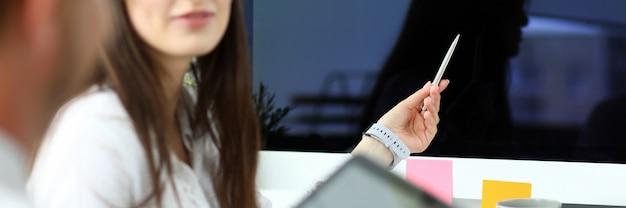 Женский кавказский работник представляя некоторые новые данные коллегам