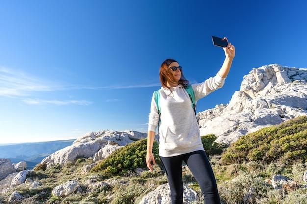 산 정상에 도달하는 여성 백인 등산객은 스마트 폰으로 자기 초상화를 찍습니다.