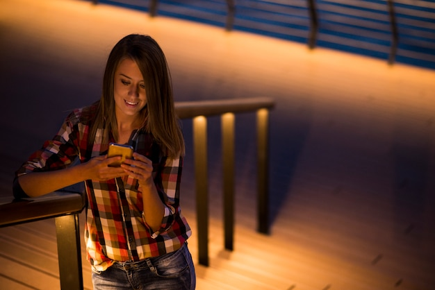 Female caucasian student reading text messages on cell phone with reflected on her face screen light, blank screen phone