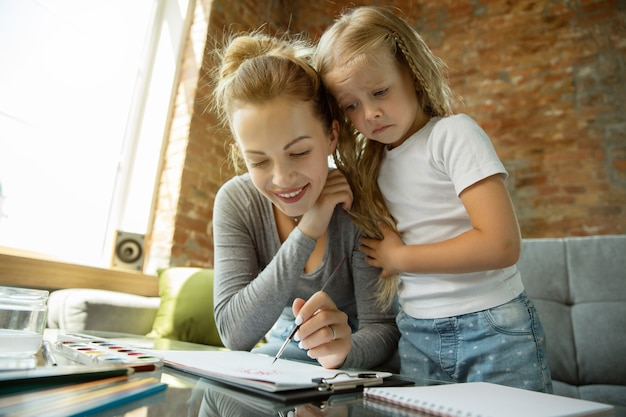 女性の白人教師と小さな女の子、またはママと娘。ホームスクーリング