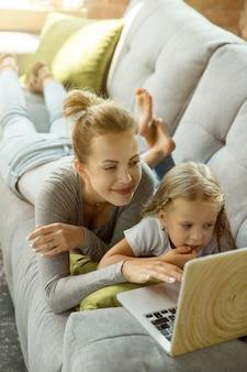 女性の白人教師と小さな女の子、またはママと娘。