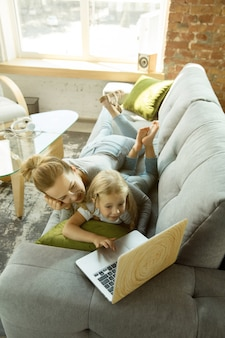 Female caucasian teacher and little girl, or mom and daughter. homeschooling