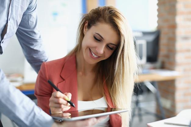 여성 ceo는 태블릿에 전자 서명을 넣습니다.