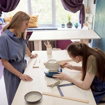 Мастер керамики и молодой ученик делают гончарные изделия в мастерской