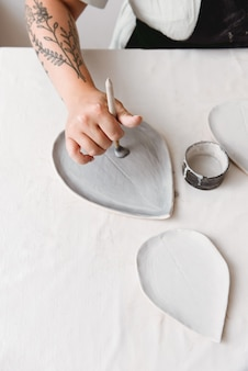 Female ceramist working by hands in pottery studio.