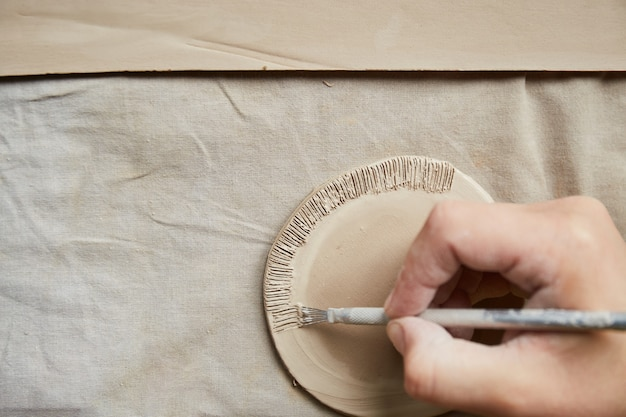 陶芸工房で働く女性陶芸家。陶芸家の手は粘土で汚れています。陶器を作るプロセス。マスター陶芸家は彼女のスタジオで働いています