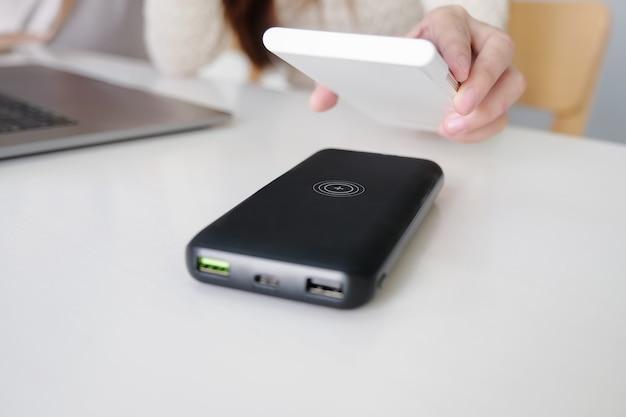 Женский смартфон зарядки с помощью портативной беспроводной быстрой зарядки на работе