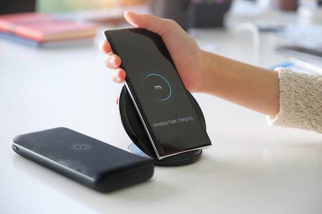 Женский смартфон с помощью беспроводной быстрой зарядки на работе