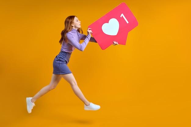 好きなものと感謝を追いかける女性、スタジオで黄色の背景に分離されたコピースペースを探しているソーシャルメディアのハートのアイコンを保持している女性