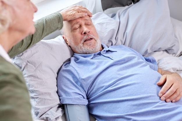 ベッドに横になっている年配の男性の発熱温度をチェックする女性。成熟した夫は、妻が額に触れて熱をチェックしている間、インフルエンザの症状を感じています。自宅で