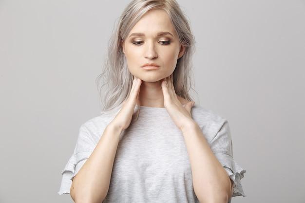 甲状腺を自分でチェックする女性。赤い斑点のある首に触れる白い t シャツを着た女性の接写。甲状腺障害には、甲状腺腫、甲状腺機能亢進症、甲状腺機能低下症、腫瘍または癌が含まれます。健康管理。